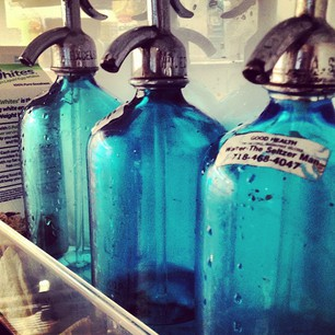 three blue glass seltzer water bottles with metal spouts in fridge door